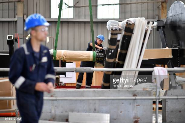 An engineer works on a communications mast for BAE Systems Type 26 frigate at Mainstay Marine Solutions' shipyard in Milford Haven in Wales on August...