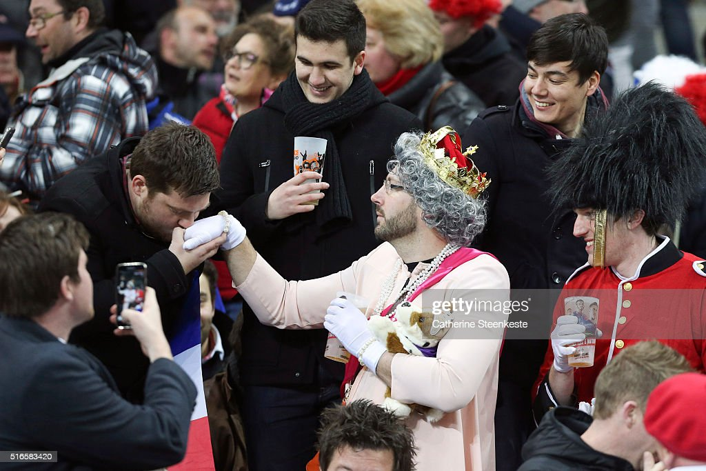 An England fan dressed as the Queen of England is greeted in the stands before the RBS Six Nations game between France and England at Stade de France on March 19, 2016 in Saint Denis near Paris, France.