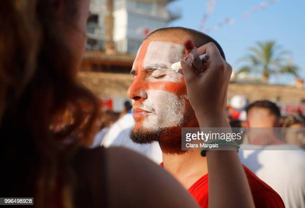 An England fan has his face painted with the flag of St George before the start of the World Cup semifinal match against Croatia on July 11 2018 in...