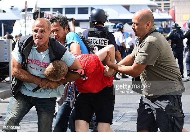 An England fan is detained by police personnel following clashes between England fans and police in the city of Marseille southern France on June 11...