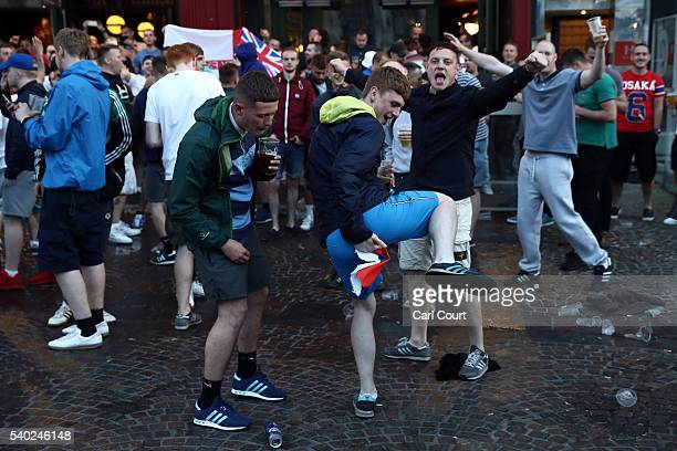 An England fan pretends to wipe his bottom with a Russian flag as English and Welsh fans chant and drink outside a pub as they gather ahead of the...