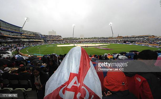 An England fan uses her flag to cover her head as the game is delayed due to rain during the ICC Champions Trophy Final match between England and...