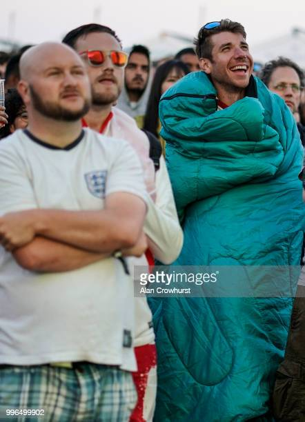 An England fan watches the match wrapped in a sleeping bag during the 2018 FIFA World Cup semi final match between Croatia and England at the Luna...