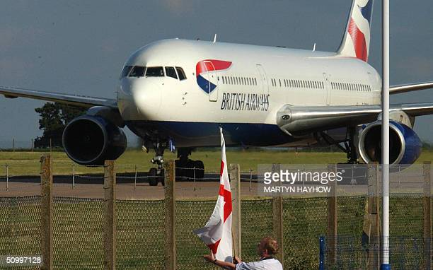 An England fan watches through the fencing at Luton Airport 25 June 2004 as the aircraft carrying the England Football squad arrives following the...