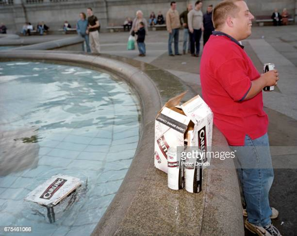 An England football fan attempts to keep his beer chilled in a fountain in London's Trafalgar Square October 2001