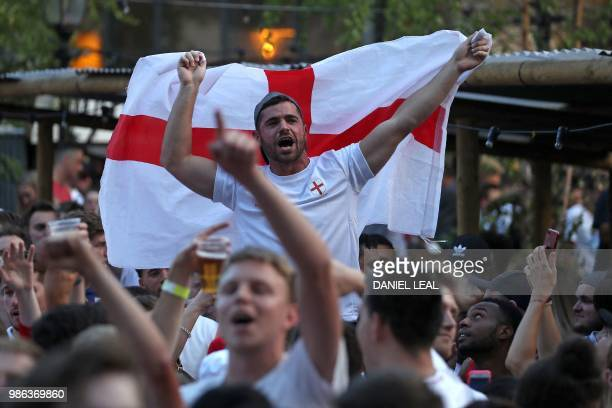 An England supporter holds up a St George's cross flag as the atmosphere builds in the Flat Iron Square pub in London ahead of the match in...