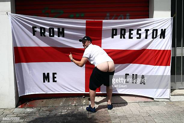An England supporter pulls his shorts down in front of an England flag hung next to a bar on June 14 2016 in Lens France Football fans from around...
