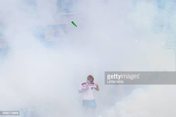TOPSHOT An England supporter walks as he is engulfed in tear gas during clashes with police in Marseille southern France on June 10 on the eve of...