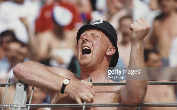 An England supporter wearing a Policeman's helmet reacts during a match against the Netherlands at the 1988 European Championships on June 15 1988 in...