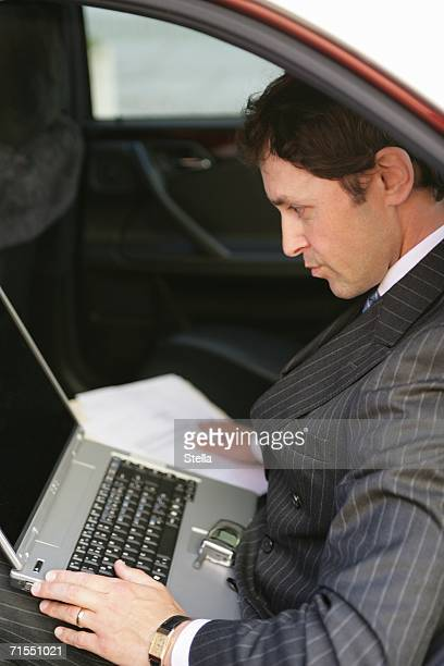 An English businessman working on a laptop in the back of a taxi