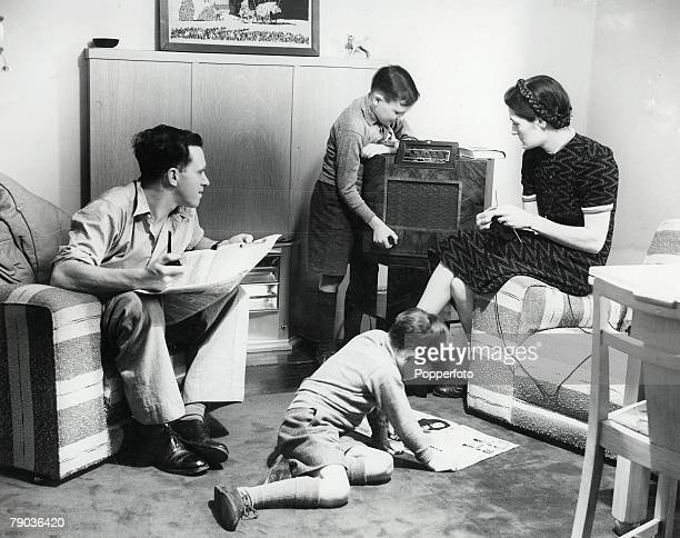 An English family relax at home, tuning in to listen to the news on the radio in their living room during World War II, circa 1940.