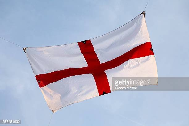 An English flag which had broken loose from one of its attaching strings flaps in the evening breeze as it flies above a pub in east London shortly...