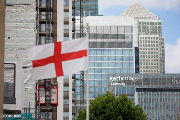 An English national flag flies in view of building work on the site of Wood Wharf a development by the Canary Wharf Group in the Canary Wharf...