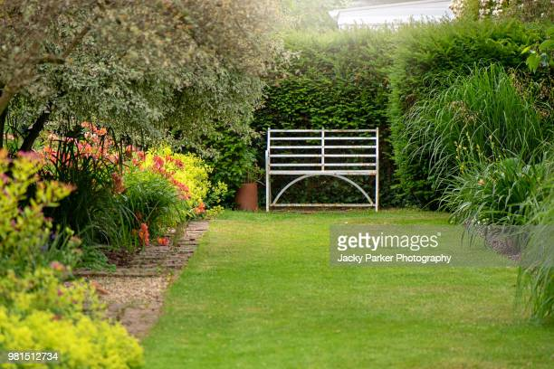 an english summer garden with a wrought iron white seat - flowerbed stock pictures, royalty-free photos & images