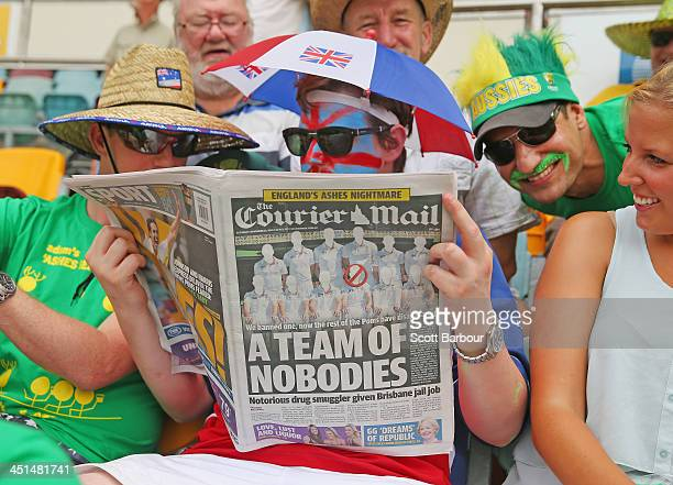 An English supporter reads a copy of the local Courier Mail newspaper during day three of the First Ashes Test match between Australia and England at...
