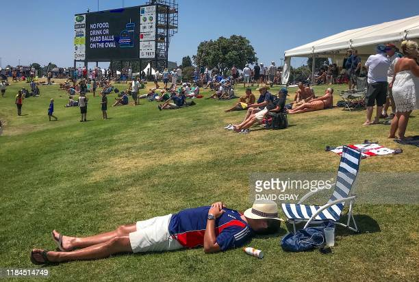 An English supporter sleeps on a grassy bank during the fifth day of the first cricket test between England and New Zealand at Bay Oval in Mount...