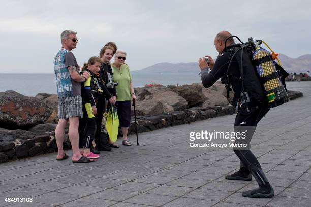 An Englishspeaking family wearing their scuba diving equipment take a picture before going into the water at Puerto del Carmen quay on April 12 2014...