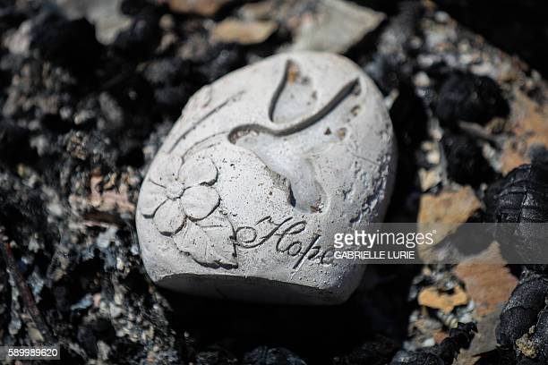 TOPSHOT An engraved stone is one of the only things remaining from a house destroyed in the Clayton Fire are seen in Lower Lake California August...