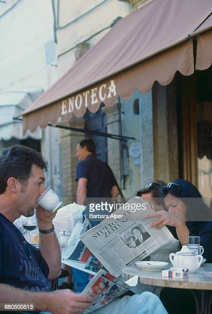 An enoteca or wine shop and street cafe in Montalcino Tuscany Italy circa 1999 One patron reads the Germanlanguage newspaper 'Stuttgarter Zeitung'