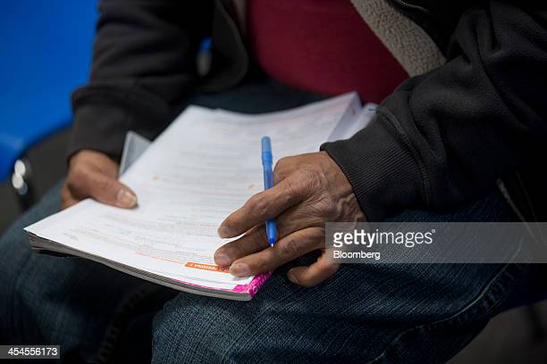 An enrollee fills out a Maryland Health Connection health insurance marketplace written application at a health insurance education and enrollment...