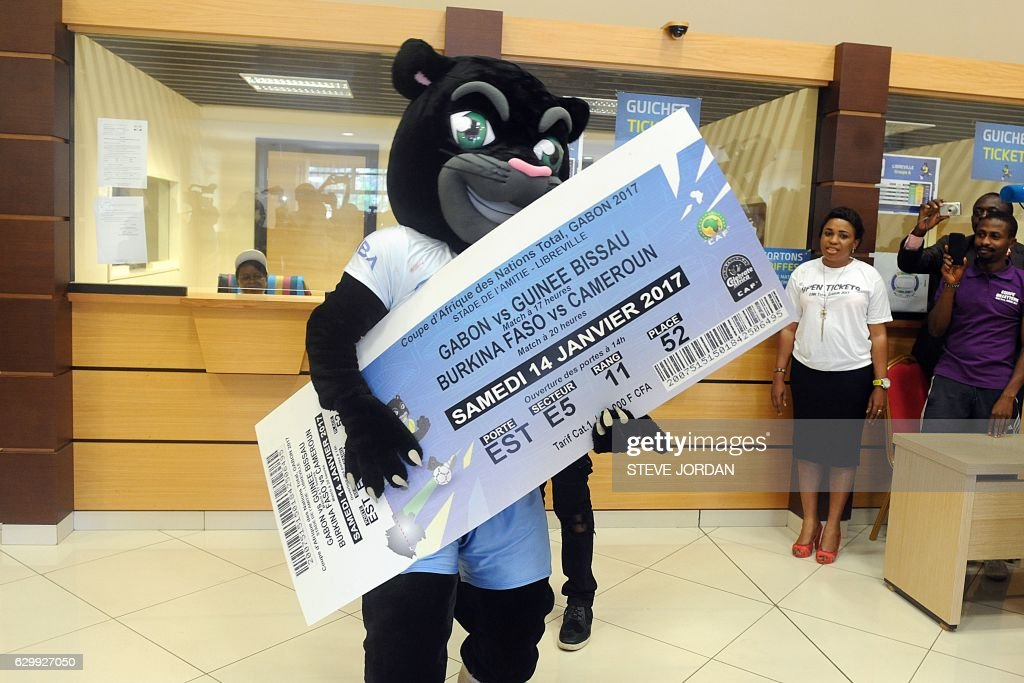 An entertainer dressed as Samba, the mascot of the 2017 African Cup of Nations, holds a giant ticket inside an office as tickets for the football tournament go on sale in Nzang-Ayong, about 33 kms from Libreville, on December 15, 2016. Gabon insists it is ready to host the African Cup of Nations, running from January 14 to February 5 next year, despite concern about the state of preparations amid political instability just one month ahead of the opening ceremony. / AFP / Steve JORDAN