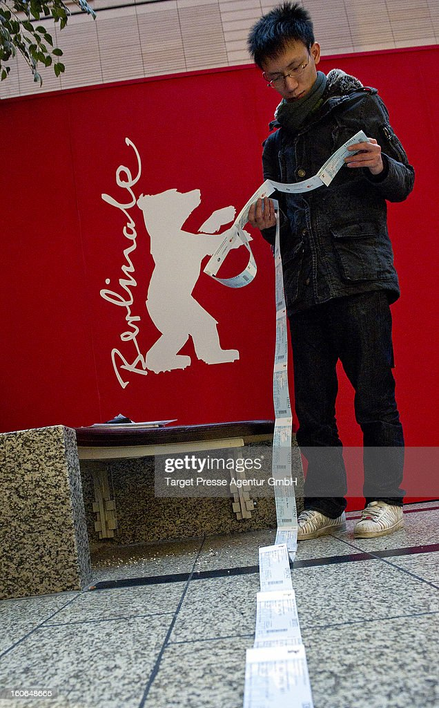 An enthusiast checks behind the ticket office his freshly bought cinema tickets for the 63rd Berlinale International Film Festival on February 4, 2013 in Berlin, Germany. The 2013 Berlinale will run from February 7-17, 2013