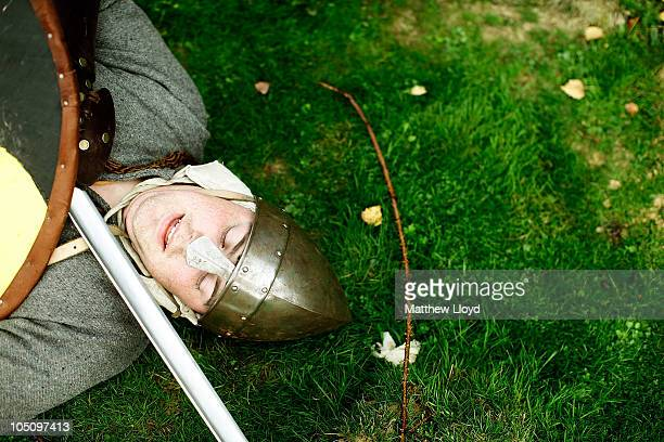 An enthusiast dressed as a warrior pretends to be slain during a reenactment of the 1066 AD Battle of Hastings on October 9 2010 in Battle near...
