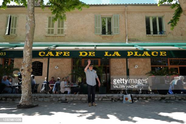 """An enthusiast plays """"petanque"""" in the shadow of a tree in front of a restaurant terrace at Saint-Paul-de-Vence, southern France on May 19 as cafes,..."""