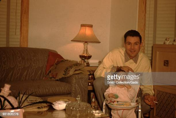 An enthusiastic father wearing a collared shirt bends down to pose with his infant daughter smiling in a living room in a suburban home holding a lit...