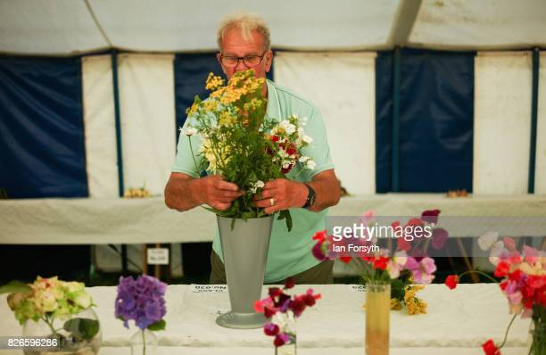 An entrant arragnes his display of flowers during the Osmotherley Country Show on August 5, 2017 in Osmotherley, England. The annual show hosts pony,...