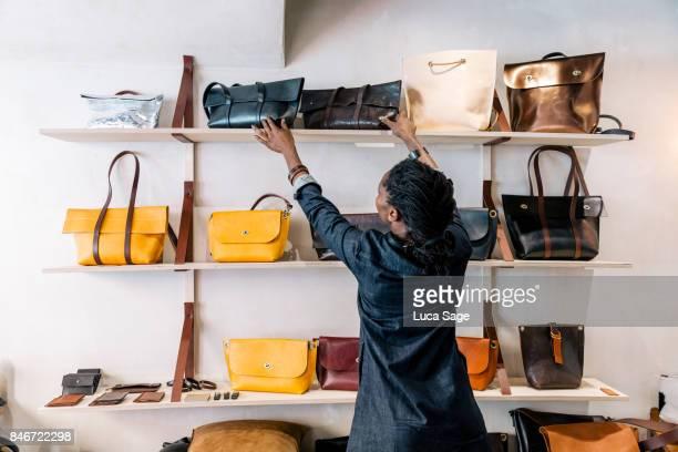 an entrepreneur handbag designer arranges her goods inside her store. - borsetta foto e immagini stock