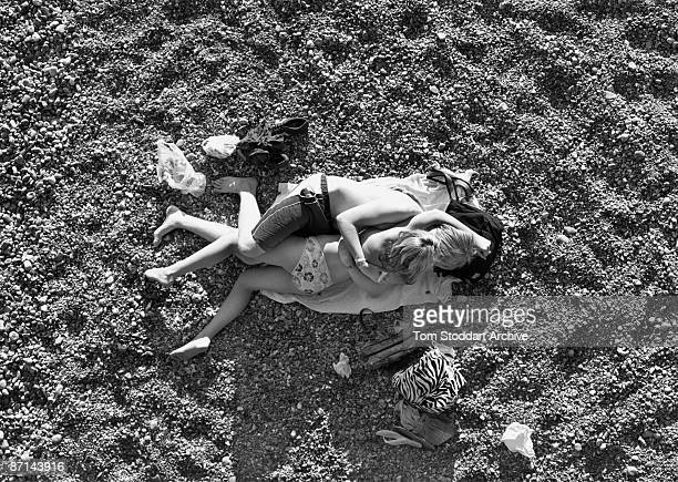 An entwined teenage couple on the beach during Bank Holiday on the Brighton seafront East Sussex August 2007