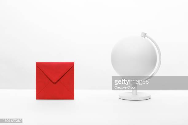 an envelope on a desktop next to a desk globe - microzoa fotografías e imágenes de stock
