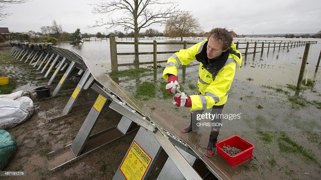 An Environment Agency worker builds flood defences around properties in Moorland in Somerset, southwest England, on February 6, 2014. Britain was lashed by more heavy rain as firefighters rescued people from flooded homes and Prime Minister David Cameron scrambled to deal with the crisis. Villages in southwest England, have been battling flooding for around five weeks as the government faced a growing tide of criticism for being too slow to aid stricken communities. According to the Environment Agency, as of January 28 65 square kilometres of land has been flooded in the Somerset Levels.