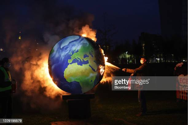 An environmental activist extinguishes a burning a model of the Earth during a climate protest over the European Central Bank funding of fossil...