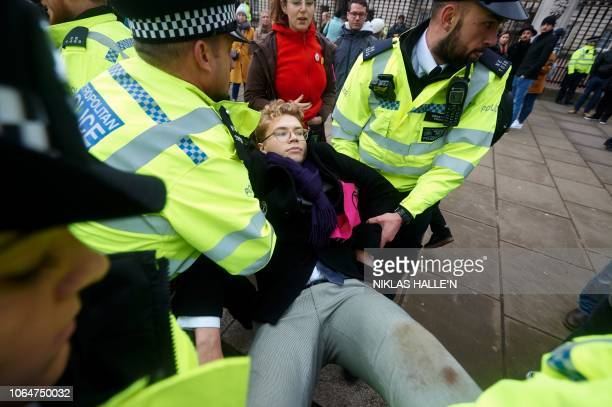 An environmental activist is carried away by police officers during a demonstration organised by the movement Extinction Rebellion outside Buckingham...