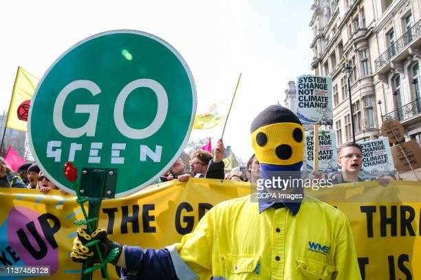 An environmental activist seen holding a placard that says go green during the demonstration at the Parliament Square Activist protest at the...