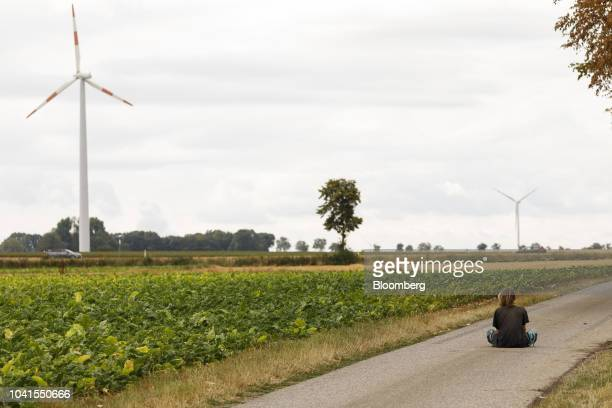 An environmental activist sits in a road as wind turbines stand beyond at the Klimacamp camp near the town of Immerath Germany on Monday Aug 13 2018...
