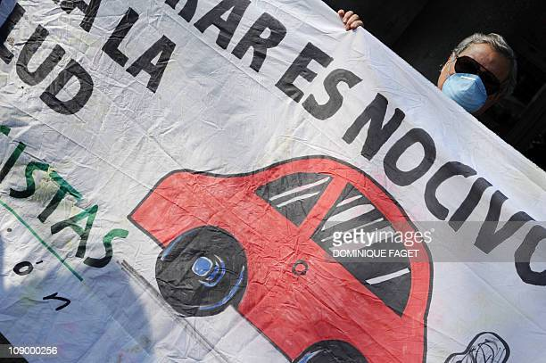 An environmental activist stands behind a banner as he demonstrates on February 11 2011 in center of madrid to demand emergency measures to clear a...
