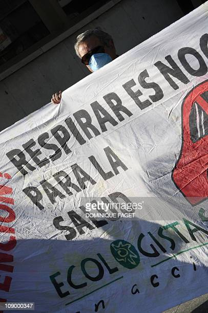 An environmental activist stands behind a banner as he demonstrates on February 11 2011 in Madrid to demand emergency measures to clear a thick layer...