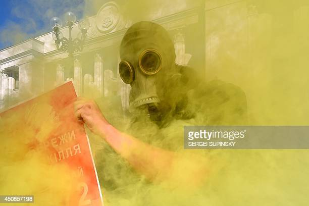 """An environmental activist wearing a gas mask holds a placard reading """"Save environment, Vote bill 4972"""", as demonstrators burn smoke bombs during an..."""