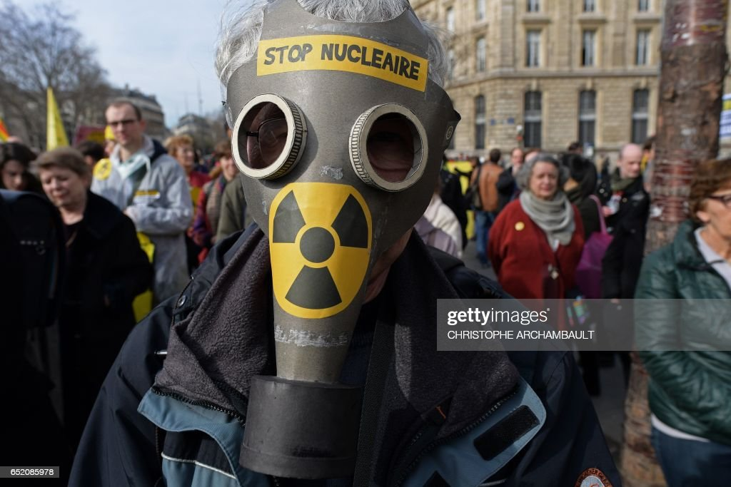 An environmental activist wearing a gas mask takes part in a demonstration called by Greenpeace and other associations to mark the 6th anniversary of the Fukushima nuclear disaster, on March 11, 2017 in Paris. /