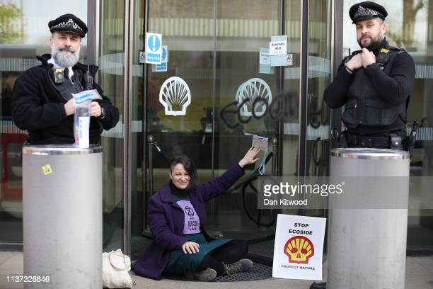 An Environmental campaigner holds up a sign saying 'my hands are glued to this surface' as she takes part in a protest outside a Shell Oil building...