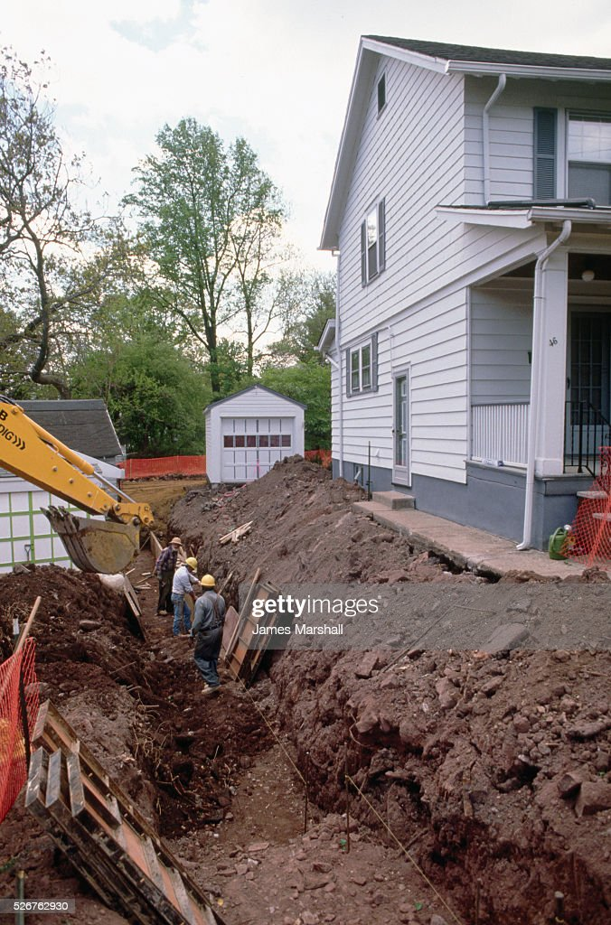 An environmental clean-up crew dig a trench next to a house in order