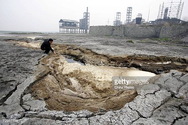 An environmental protection worker checks dried pollutants at the Dongting Lake Protective Area in Jiangjiazui Township on January 11 2007 in Hanshou...