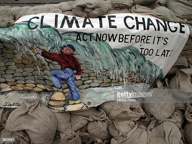 An environmental protest banner hangs on a the 500 meter dike November 18 2000 outside the 6th United Nations Conference on Climate Control in The...