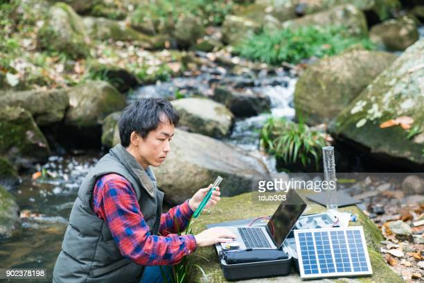 an environmental researcher monitoring water quality from a solar powered field laboratory - environmentalist stock pictures, royalty-free photos & images