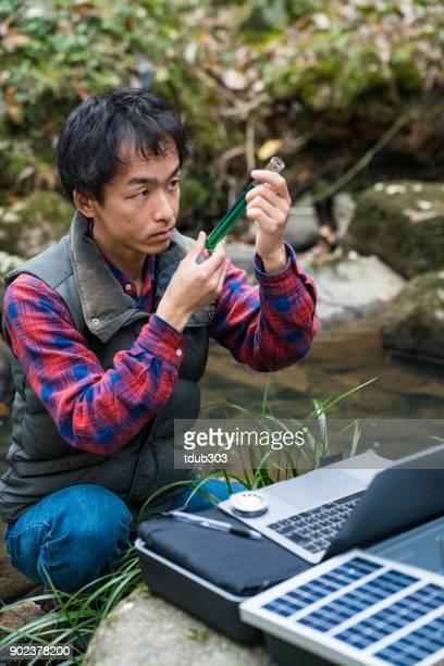 Een milieu onderzoeker toezicht op de kwaliteit van het water van een zonne-aangedreven veld laboratorium