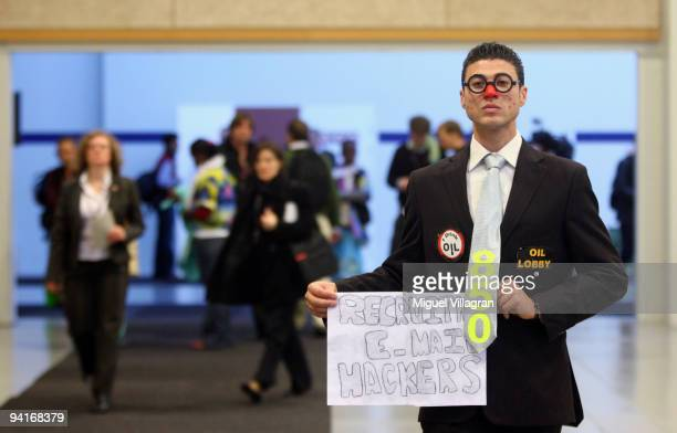 An environmentalist disguised lika a mock lobbyist holds a banner reading 'Recruting email hackers' during the third day of the United Nations...