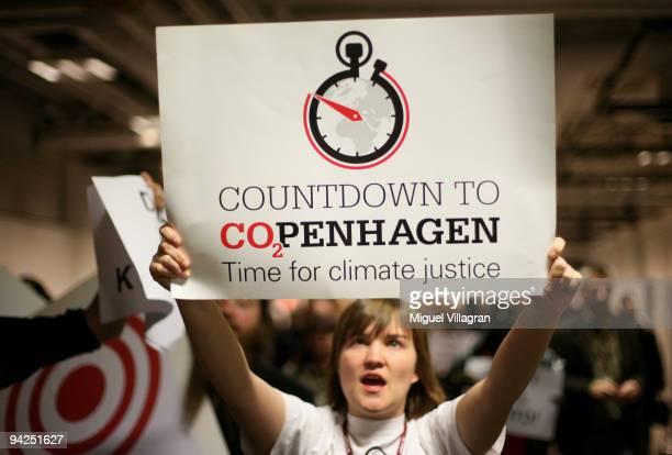 An environmentalist holds a banner reading 'Countdown to CO2PENHAGEN Time for climate justice' during the fourth day of the United Nations Climate...